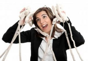woman holding various corded phones to her head